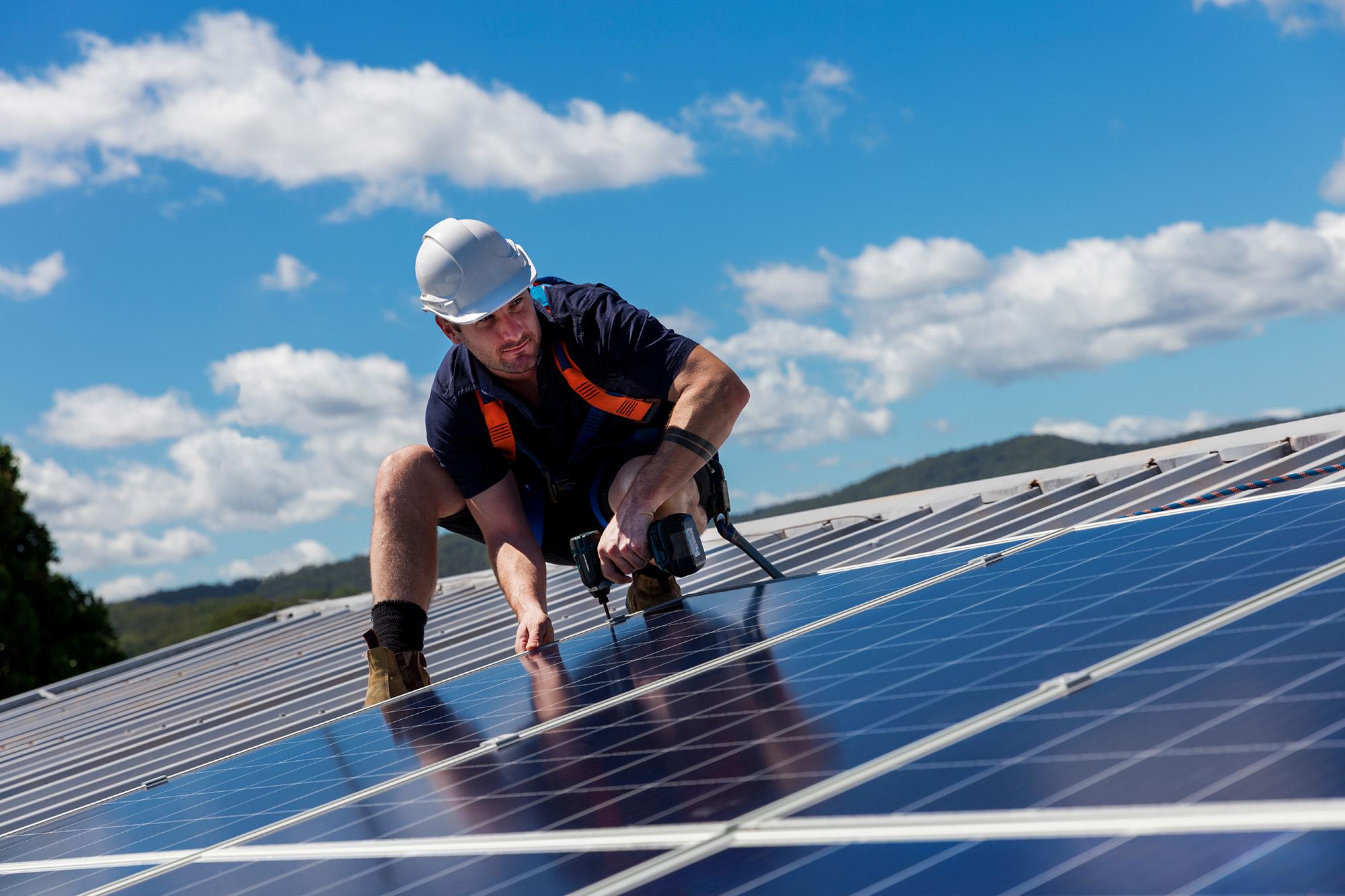 Un installateur sur un toit installe des panneaux photovoltaique SYSTOVI